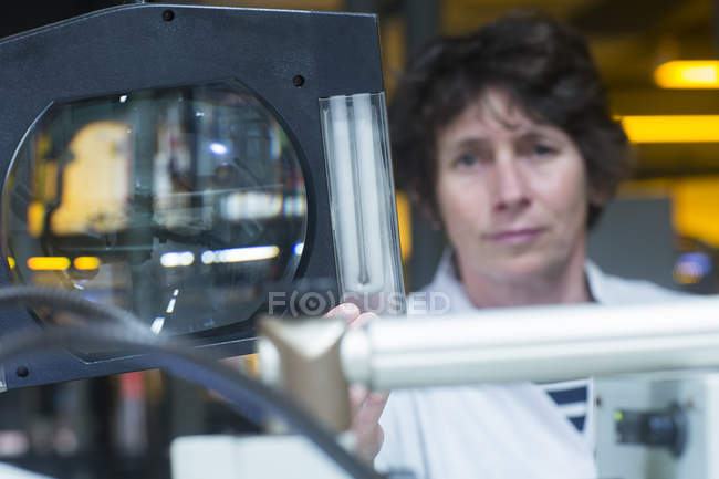 Optical lens and female worker — Stock Photo