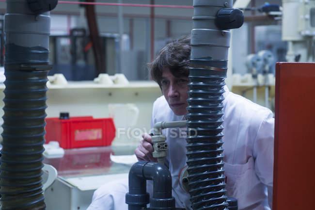 Woman in lab coat adjusting equipment — Stock Photo