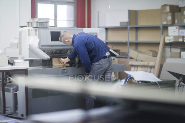 Young worker starting printing process — Stock Photo