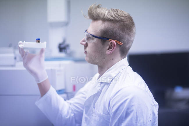 Scientist examining test tubes — Stock Photo