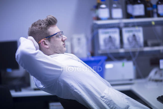 Scientist relaxing on chair at modern laboratory — Stock Photo
