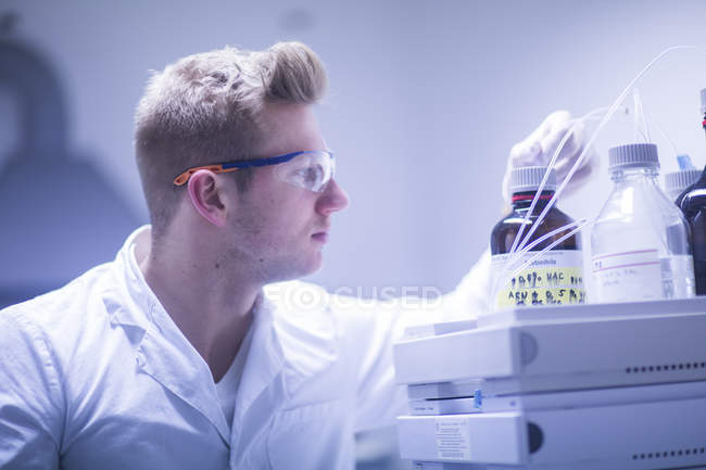 Scientist researching bottles with liquid — Stock Photo