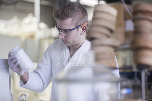 Scientist looking at bottle with liquid — Stock Photo