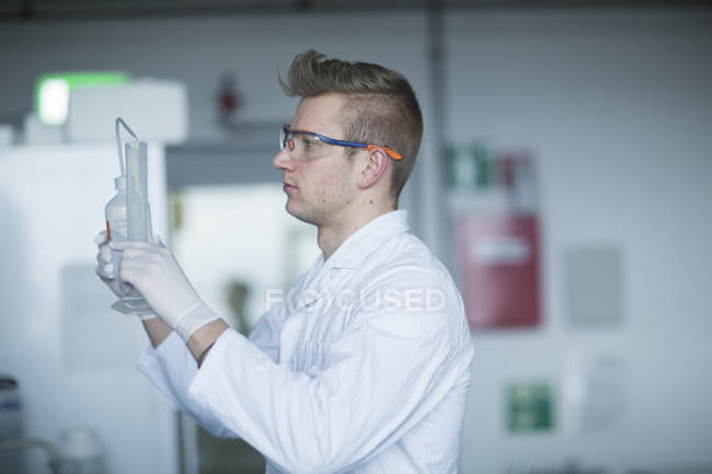 Scientist holding laboratory flask — Stock Photo