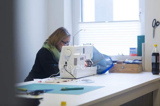 Woman working on sewing machine — Stock Photo