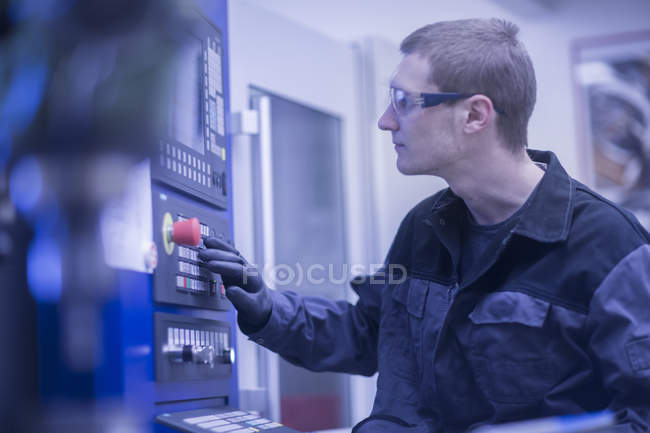 Engineer pressing button on electronic machine — Stock Photo