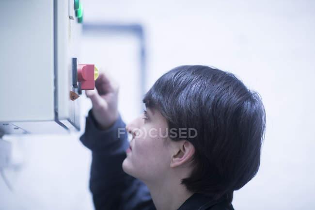 Female engineer adjusting machinery equipment — Stock Photo
