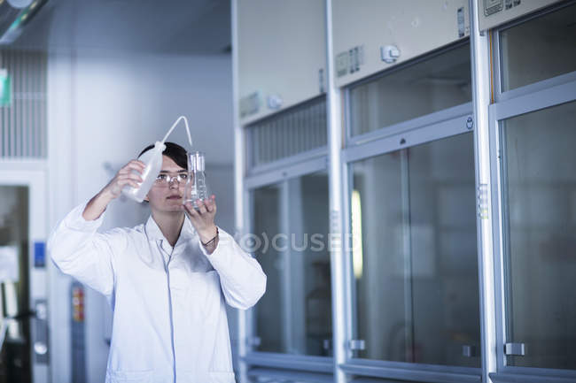 Female scientist pouring liquid in flask — Stock Photo