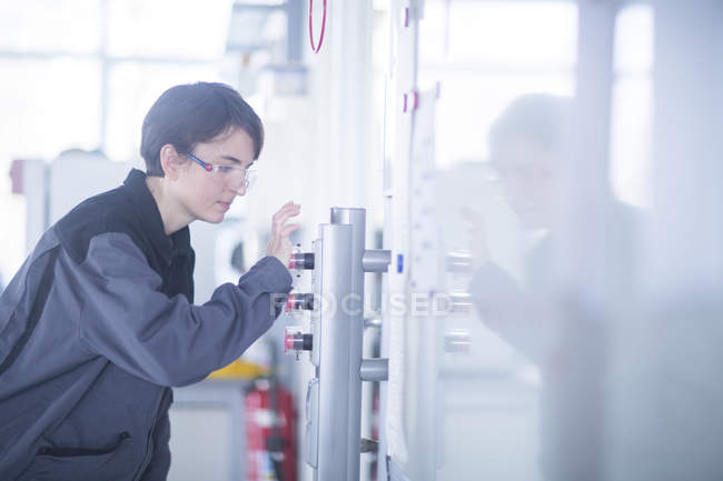 Female engineer adjusting machinery equipment — Stock Photo