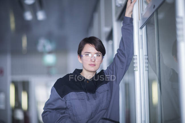 Engineer standing near shelves and looking at camera — Stock Photo