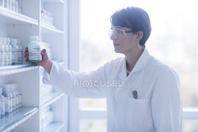 Scientist taking container with pills from shelf — Stock Photo