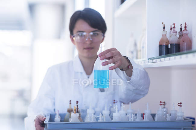Scientist examining flask with liquid in laboratory — Stock Photo