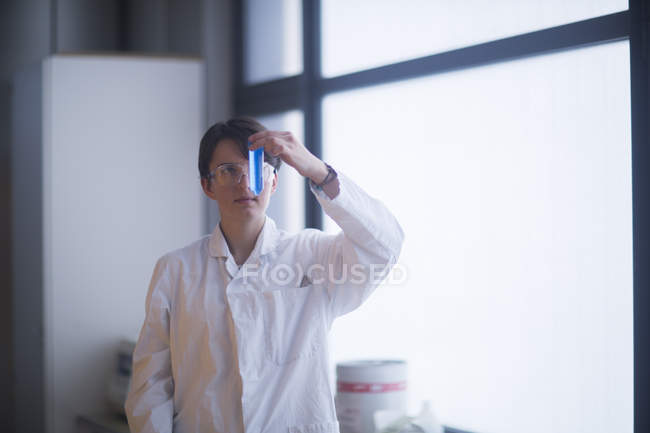 Scientist examining test tube with blue liquid — Stock Photo
