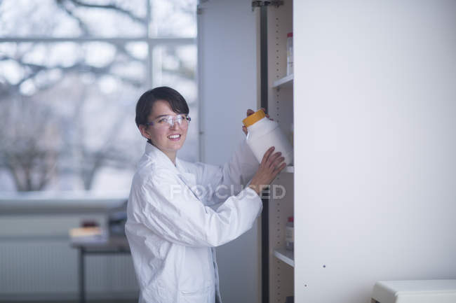 Female scientist taking container from shelf — Stock Photo