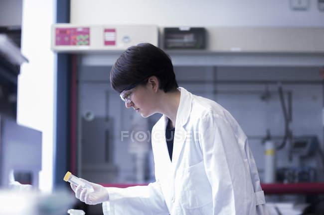 Tube à essai tenue scientifique féminin — Photo de stock