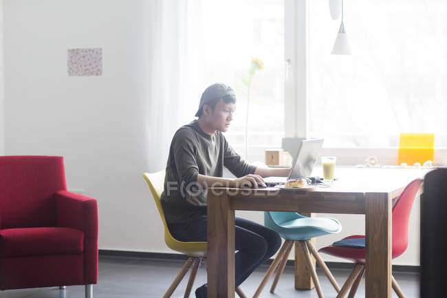 Man working on laptop computer at home — Stock Photo