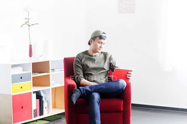 Людина сидить на стільці і дивитися фільми на планшет — стокове фото