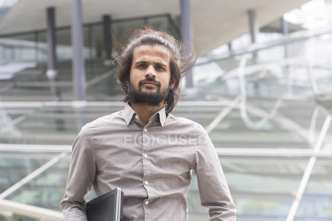 Businessman standing with laptop in hand — Stock Photo