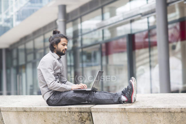 Businessman sitting on parapet and working on laptop — Stock Photo