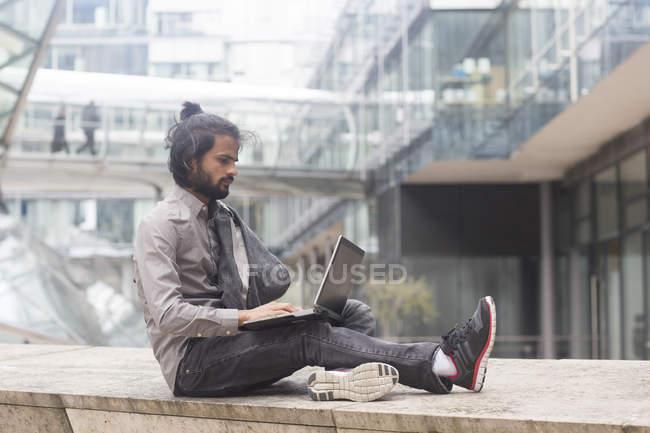 Бізнесмен, сидячи на парапету і працюють на ноутбук — стокове фото