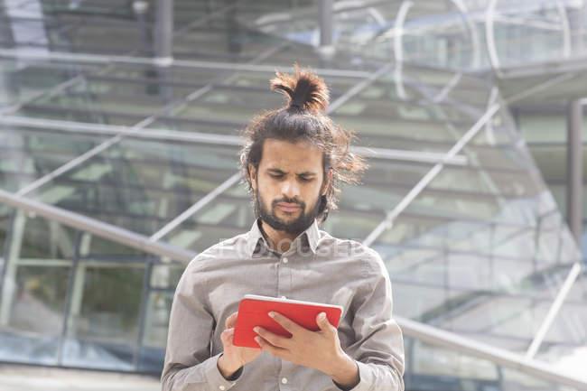 Бизнесмен стоя и с помощью цифрового планшета — стоковое фото