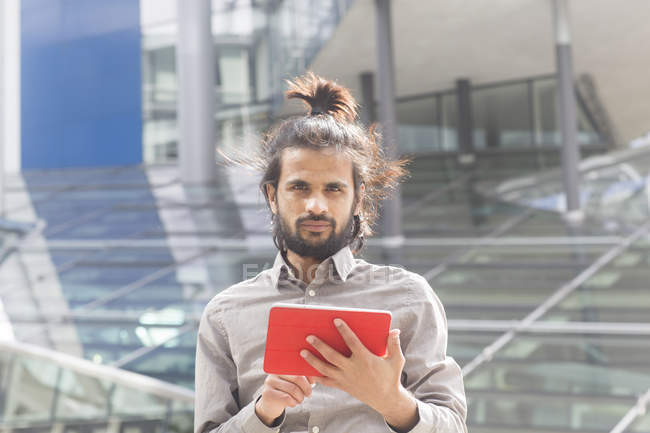 Businessman standing and using digital tablet — Stock Photo