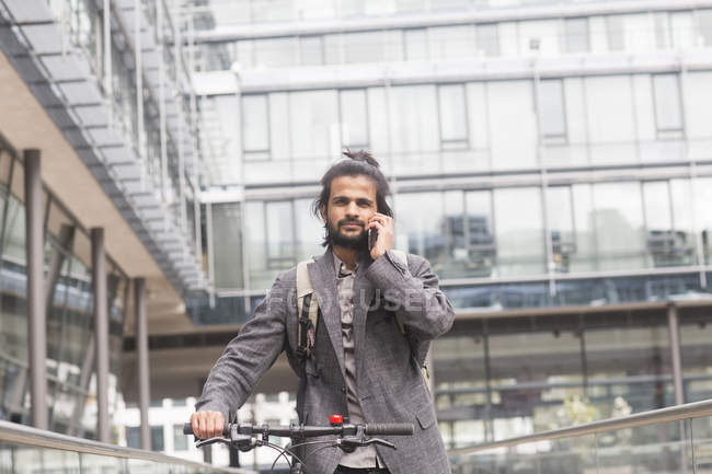 Бизнесмен, говоря на смартфоне во время езды на велосипеде — стоковое фото