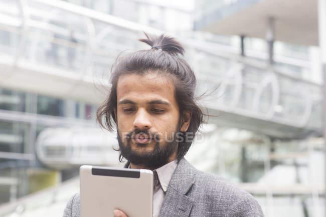Homme d'affaires debout et utilisant une tablette numérique — Photo de stock