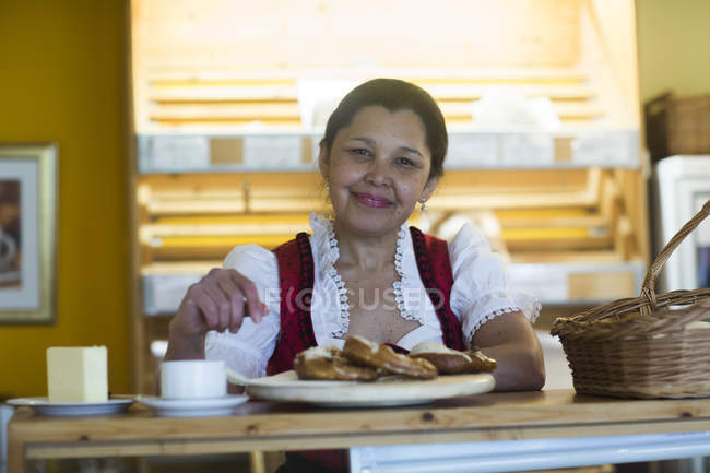 Woman standing near counter in small bakery — Stock Photo