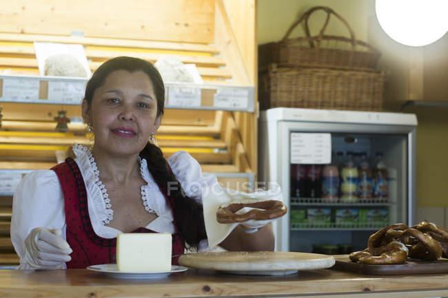 Mulher em pé perto de contador em pequena padaria — Fotografia de Stock