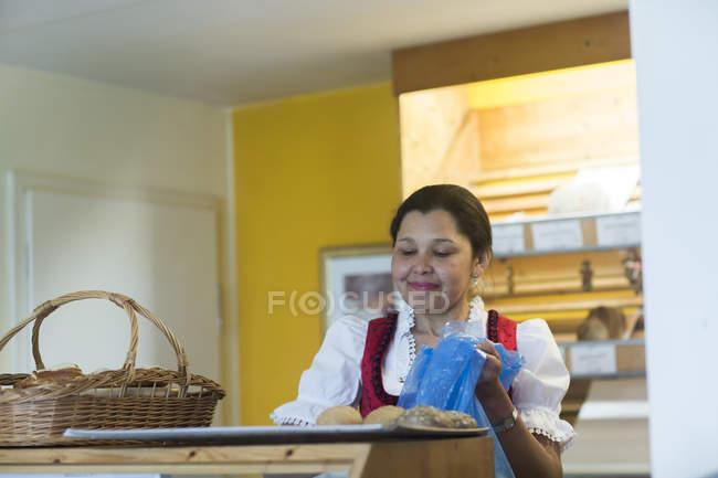Trabalhador de padaria colocando pães na bandeja — Fotografia de Stock