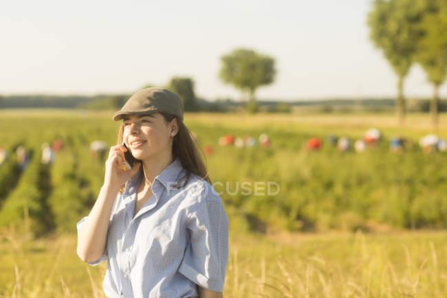 Woman farmer talking on phone — Stock Photo