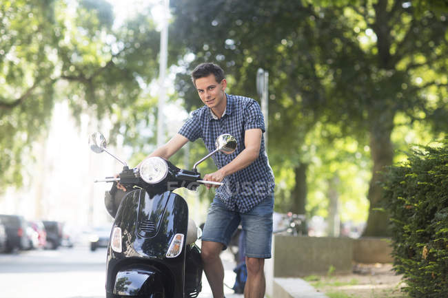 Young man standing near scooter — Stock Photo