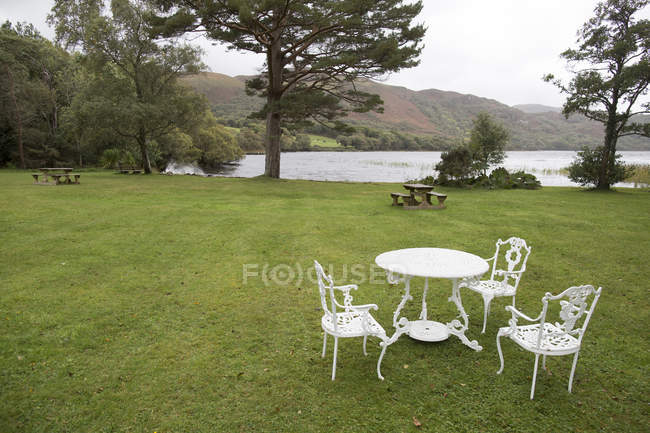 Table with chairs in green yard — Stock Photo