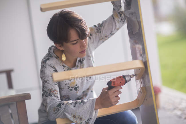 Woman making upcycling chair — Stock Photo