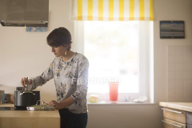 Donna che cucina la cena nella cucina — Foto stock