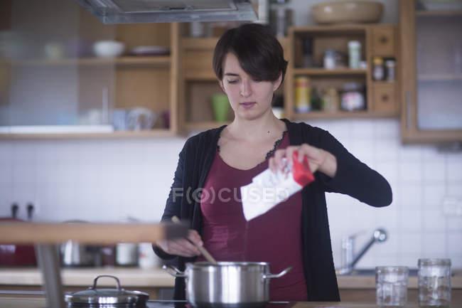 Donna aggiungendo zucchero di pan — Foto stock