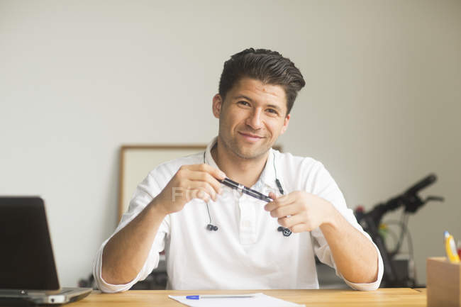 Male manager looking in camera, smiling and holding pen — Stock Photo