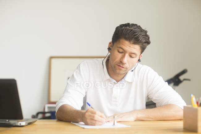 Male manager writing on workplace — Stock Photo