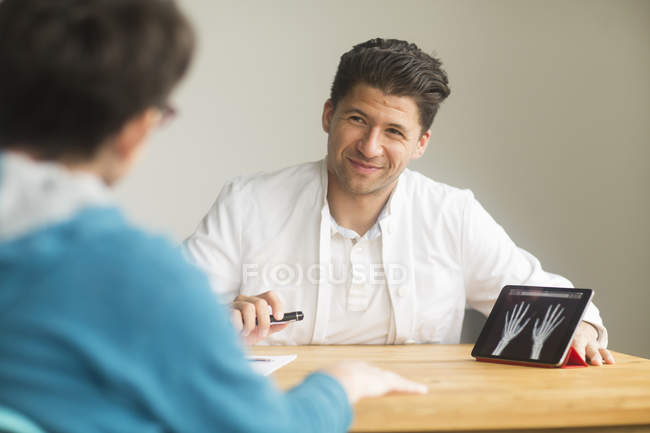 Male radiologist smiling while talking with female patient — Stock Photo