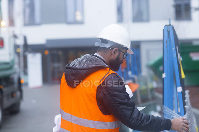Rear view of male civil engineer checking equipment — Stock Photo