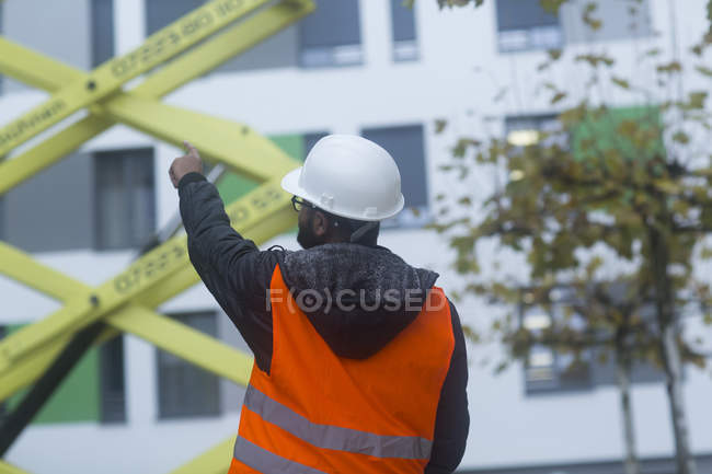 Rear view of male civil engineer checking machinery equipment — Stock Photo