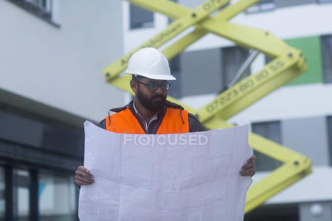 Masculino engenheiro civil olhando planta no canteiro de obras — Fotografia de Stock