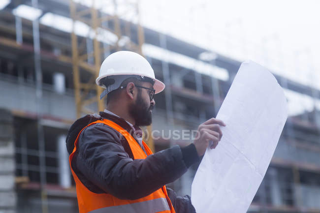 Male civil engineer looking at blueprint on construction site — Stock Photo
