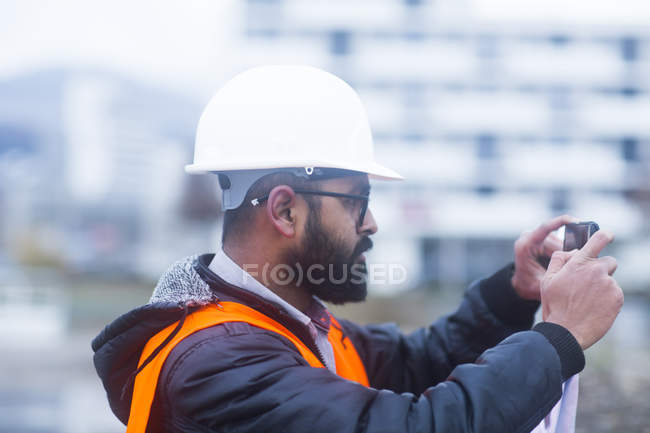 Male civil engineer taking photo with smartphone — Stock Photo