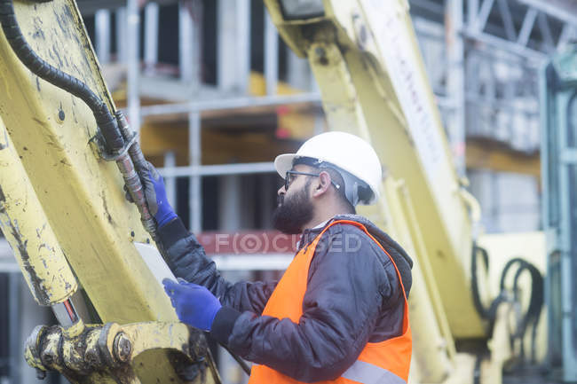 Male civil engineer checking machinery equipment — Stock Photo