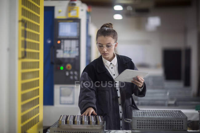 Female engineer examining machinery with digital tablet — Stock Photo