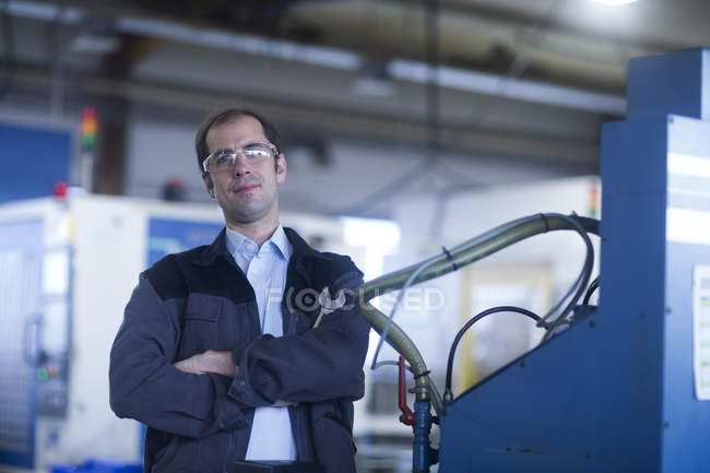 Front view of male engineer standing at industrial plant — Stock Photo