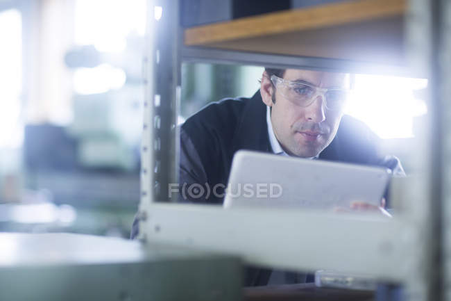 Male engineer inspecting equipment with digital tablet — Stock Photo