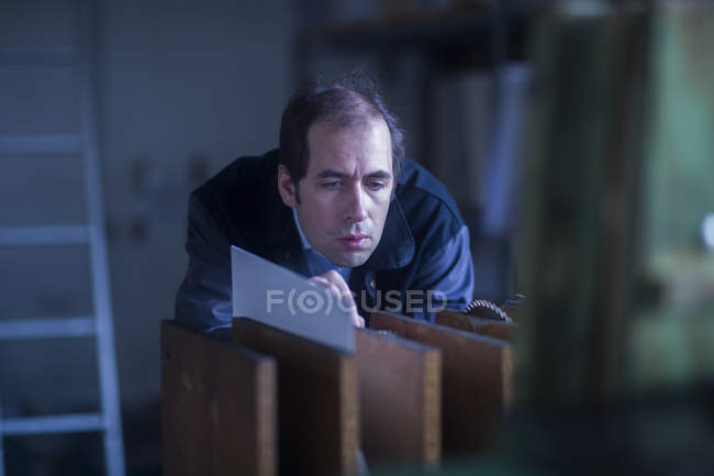 Male engineer examining machinery at industrial plant — Stock Photo